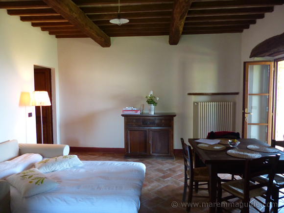Living/dining room of Tuscan farmhouse apartment for sale.
