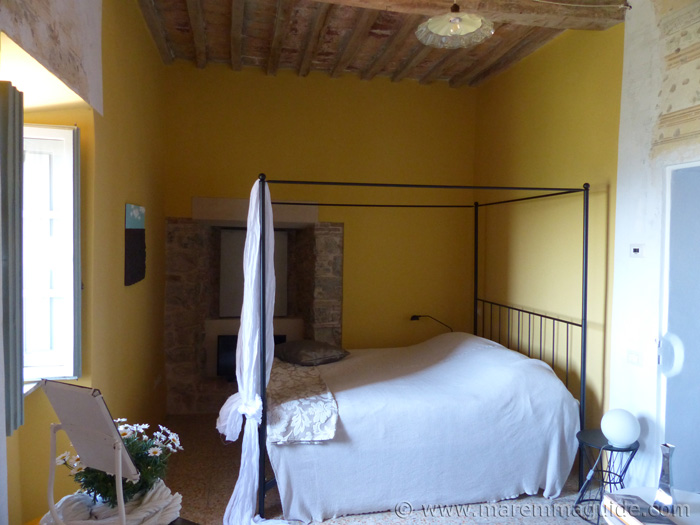 Boutique apartments Tuscany: double bedroom with a view and four poster bed.