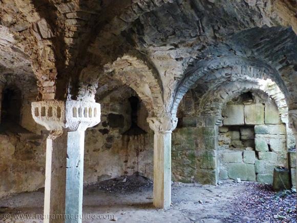 Cubic and Corinthian capitals and columns in the Cripta di Giugnano.