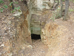 Etruscan chamber tomb cut into an old quarry face in the woods at Buca delle Fate, Maremma Tuscany
