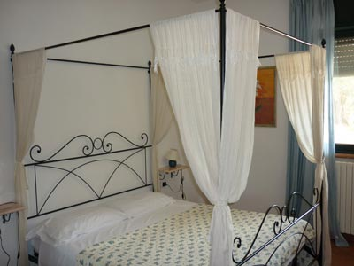 Follonica villa apartment bedroom with four poster bed