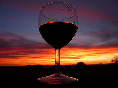 Glass of red wine at sunset