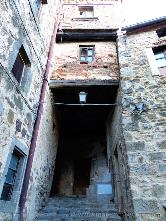 Medieval buildings still lived in in Montelaterone with 90 degree dark alleyway beneath