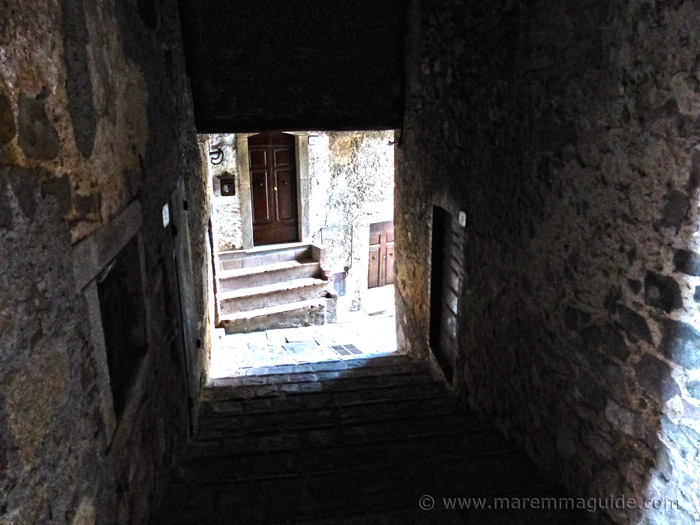 Dark medieval alleyway with building above in Montelaterone.
