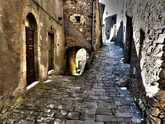 Stone-paved medieval street dividing in two with arch in Montelaterone