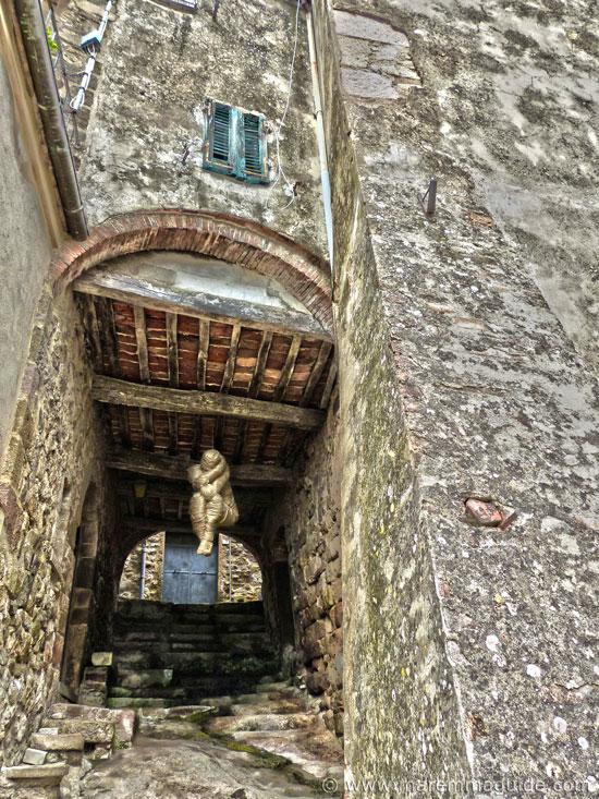 Mostra La Rocca Roccatederighi human sculpture in wool in medieval alleyway