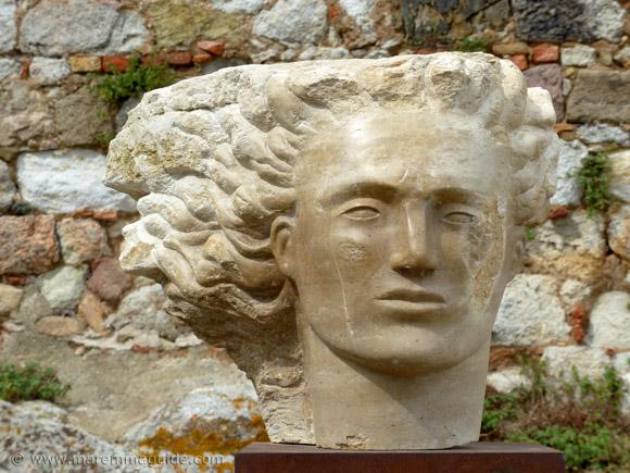 Marble head sculpture Mostra La Rocca Roccatederighi behind the Chiesa di San Martino Vescovo.