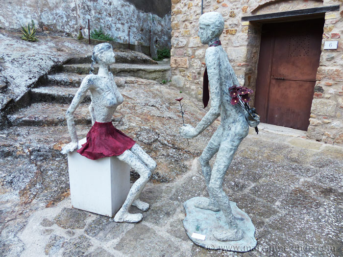 Mostra La Rocca Roccatederighi Tuscany. Gallant man giving flower to girl stautes.