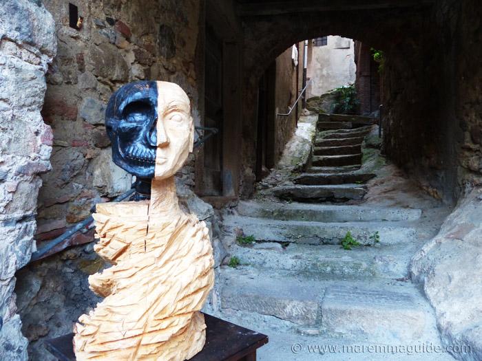 Mostra La Rocca Roccatederighi: skull sculpture in wood.