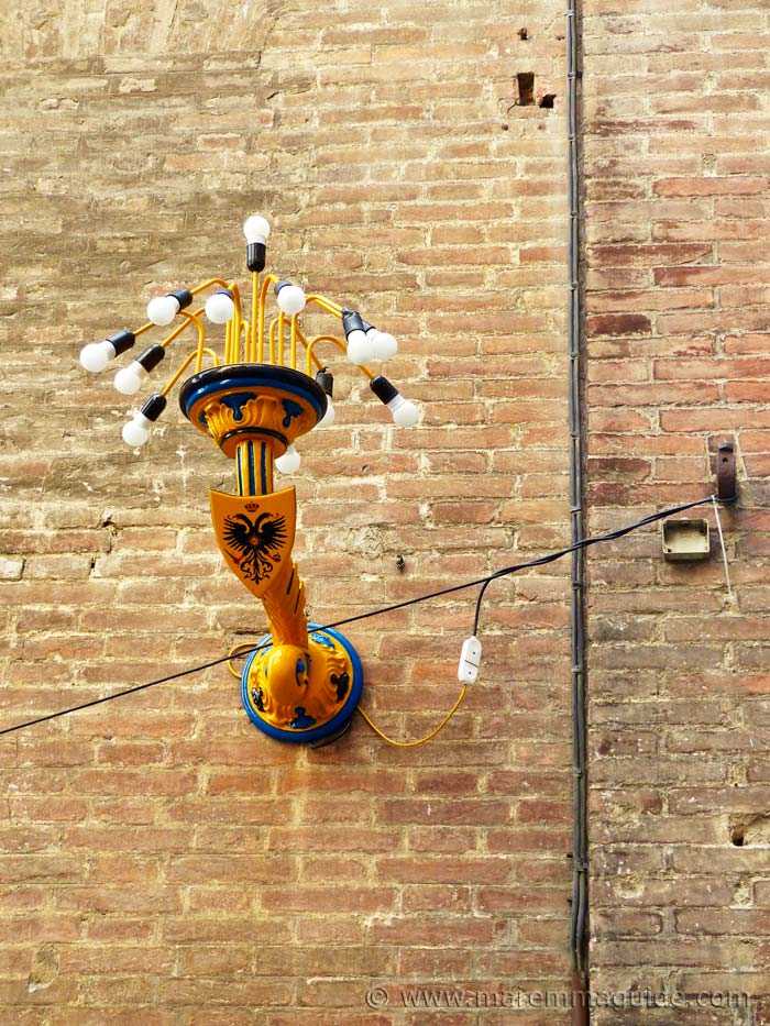 Nobile Contrada dell'Aquila Siena light fixing in street.