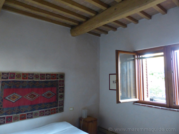 Restored Tuscany farmhouse bedroom with wooden beamed ceiling