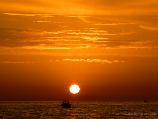 Orange ocean sunset at Castiglione della Pescaia, Tuscany: fishing boats coming home