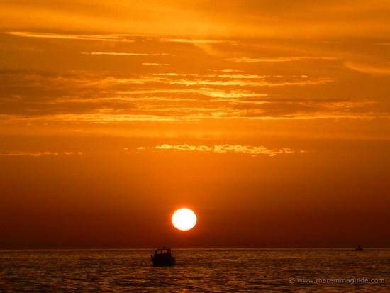 Orange ocean sunset at Castiglione della Pescaia, Tuscany: fishing boats coming home