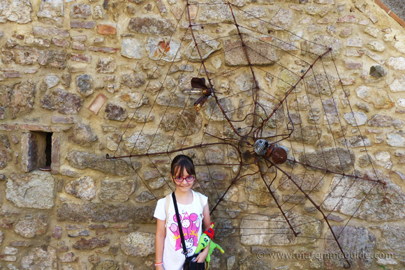 Outdoor metal wall art, spider, web and fly, in Tuscany Italy