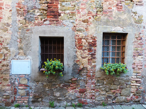 Windows with flowers inside Pereta's medieval castle.