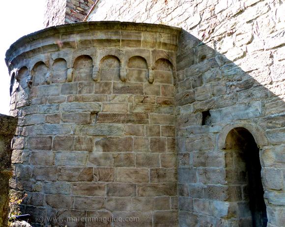 Apse of the Pieve di Santa Mustiola in Sticciano with stone Romanesque faces