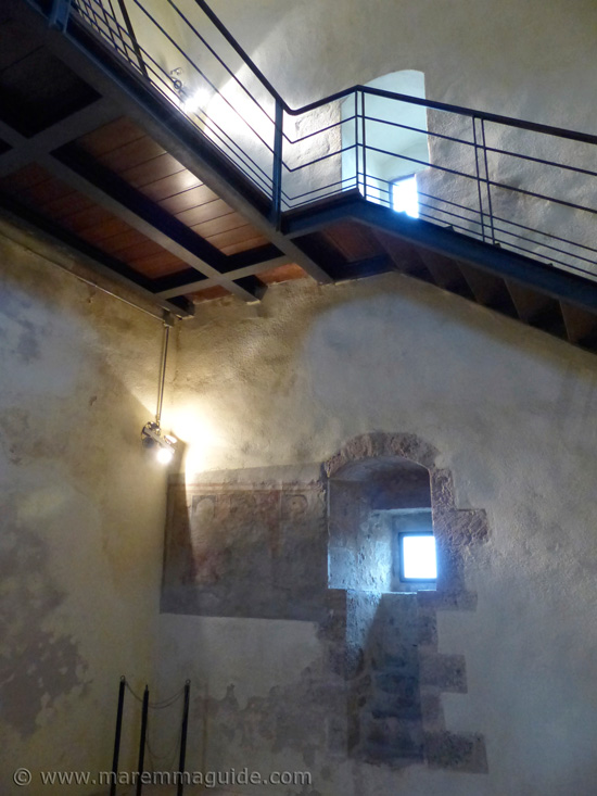 Inside Capalbio's castle tower: the steps up and the recently discovered 15th century fresco of Madonna and child with saints.