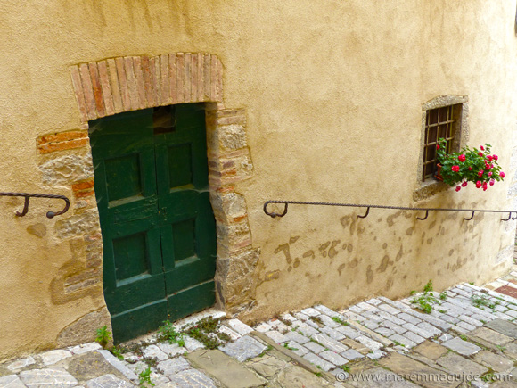 Green Tuscany door with window flowers in Roccalbegna