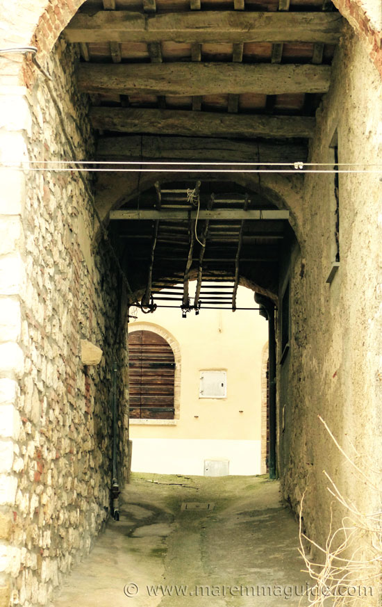 Handmade ladders hanging in an arched entrance into Semproniano