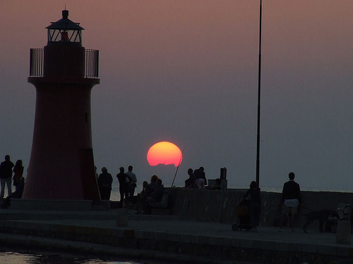 Tuscany sunset scenes: people in the sunset at the Castiglione della Pescaia lighthouse, Maremma