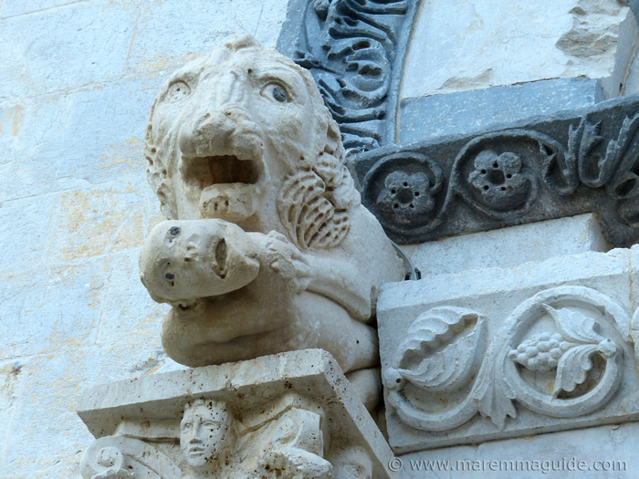 Romanesque stone lion with anthropomorphous prey in its claws.