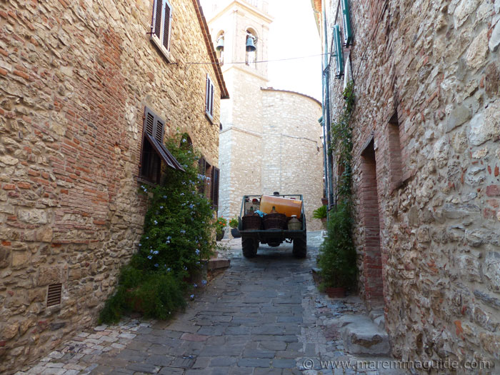 Tractor carrying wine and oil along a narrow medieval street in Suvereto Maremma Tuscany.