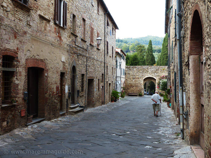 Old man taking a walk in Suvereto Tuscany.