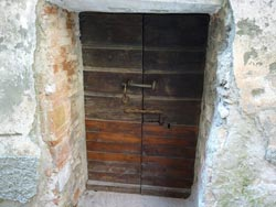 A medieval door within deep stone walls in Tatti, Maremma Italy