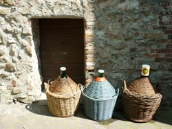 A tiny cellar door in medieval Tatti and wine bottles, Maremma Italy