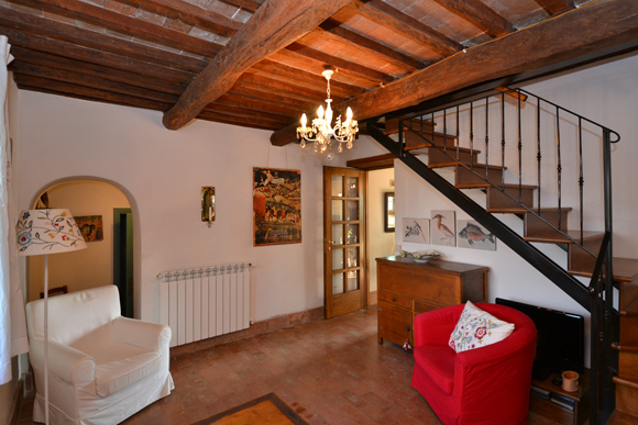 Tuscany cottage for sale: living room with terracotta floor and wooden beamed ceiling..
