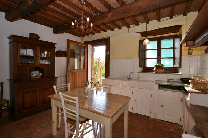 Tuscany cottage for sale: traditional Tuscan countryside kitchen with fireplace and butler sink.