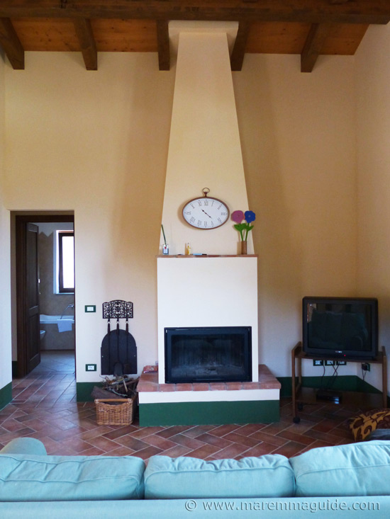 Maremma holiday house: cottage living room with fireplace.