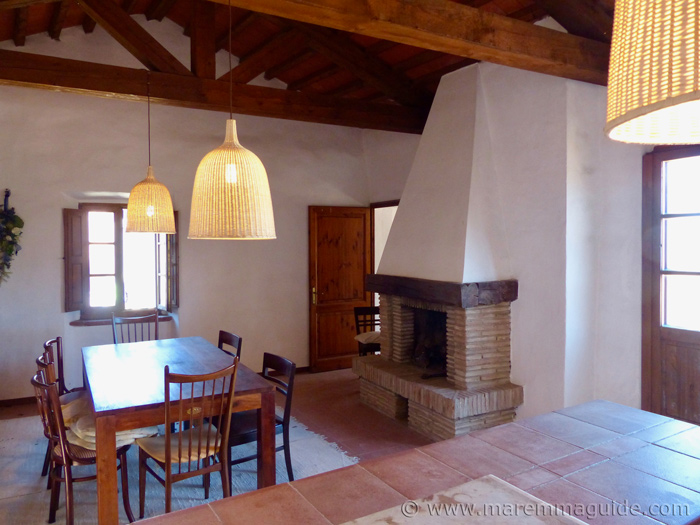 Open fireplace, kitchen and dining area.