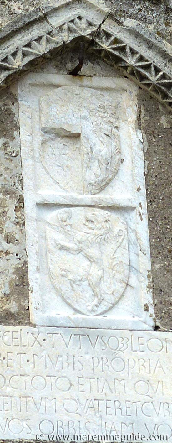 Capalbio Italy coat of arms: Sienese lion and bald head with Latin inscription detail dated 1418..