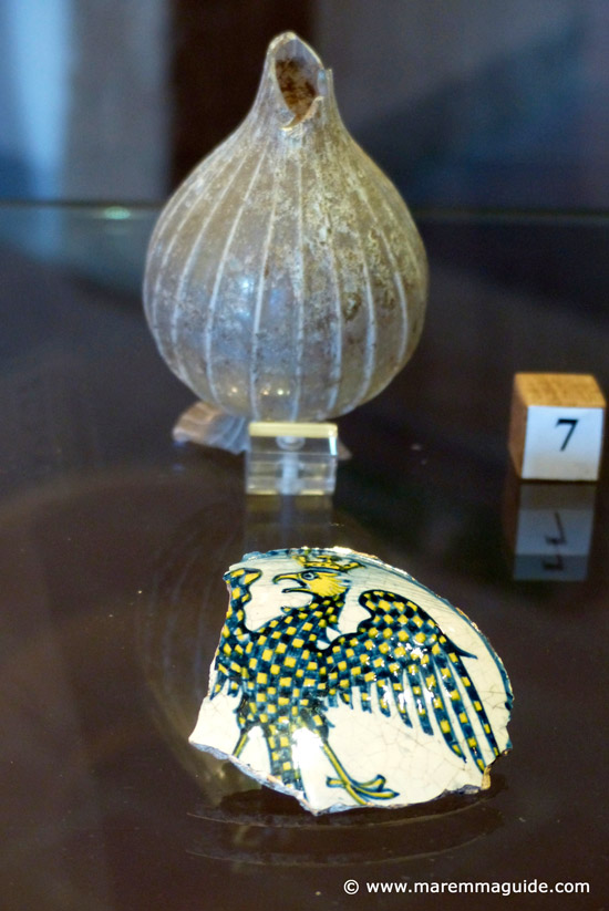 Part of a wedding plate commissioned by the family of Elena di Giovanni Conti of Montelanico - the daughter of the Counts of Montelanico - upon her engagement to Niccolo III Orsini and a medieval glass perfume bottle.