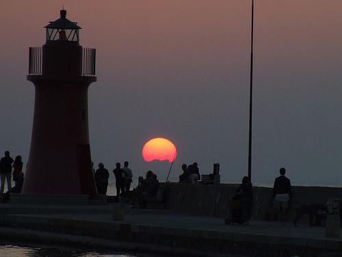 Tuscany sunset scenes: people in the sunset at the Castiglione della Pescaia lighthouse, Maremma
