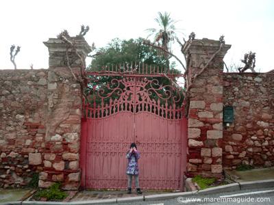 Pink wrought-iron Tuscan gate in Bolgheri Maremma